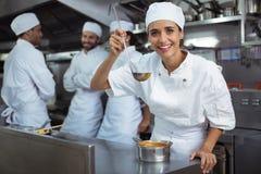 Δοκιμάζοντας τρόφιμα αρχιμαγείρων από το κουτάλι στην κουζίνα στο εστιατόριο Στοκ Εικόνες