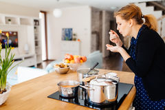Δοκιμάζοντας τρόφιμα νοικοκυρών που γίνονται στην κουζίνα Στοκ εικόνες με δικαίωμα ελεύθερης χρήσης