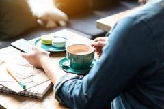 Δοκιμάζοντας φλιτζάνι του καφέ γυναικών στον πίνακα Στοκ Εικόνες
