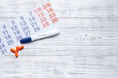 Δοκιμή εγκυμοσύνης κοντά στο ημερολόγιο και τα χάπια στην ξύλινη τοπ άποψη υποβάθρου copyspace Στοκ Εικόνα