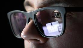 Δοκιμή ματιών και έννοια διαγωνισμών Κλείστε επάνω του ατόμου με τα γυαλιά Στοκ Εικόνα