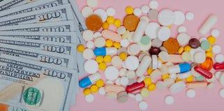 Δολάρια και χάπια σε ένα ρόδινο υπόβαθρο Η ιατρική συνταγών στα δολάρια για την έννοια βιομηχανίας φαρμάκων του υψηλού κόστους γι Στοκ Φωτογραφίες