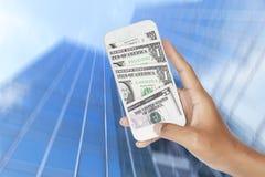 Δολάρια μέσα στο smartphone με θολωμένη την περίληψη κίνηση του σύγχρονου κτηρίου γυαλιού Στοκ εικόνα με δικαίωμα ελεύθερης χρήσης