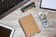 Δολάρια με τα αντικείμενα γραφείων στον ελαφρύ ξύλινο πίνακα Στοκ εικόνες με δικαίωμα ελεύθερης χρήσης