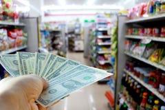 Δολάρια μιας χεριών εκμετάλλευσης στο κατάστημα Στοκ Εικόνες
