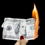 100 δολάρια που καίνε σε ένα μαύρο υπόβαθρο Στοκ Εικόνα