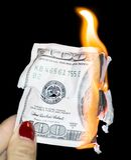 100 δολάρια που καίνε σε ένα μαύρο υπόβαθρο Στοκ Εικόνες