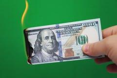 100 δολάρια που καίνε σε ένα πράσινο υπόβαθρο Έννοια της μείωσης στην οικονομία και την απώλεια στοκ φωτογραφίες με δικαίωμα ελεύθερης χρήσης