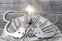 Δολάρια, χειροπέδες, βολβός σε ένα ξύλινο υπόβαθρο στοκ εικόνες
