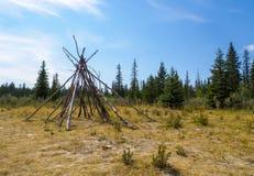 Δομή Tipi κούτσουρων σε ένα καθαρισμένο έξω μπάλωμα της χλόης στη φύση Στοκ εικόνες με δικαίωμα ελεύθερης χρήσης