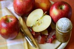 Δονητής ζάχαρης, μήλα και μαχαίρι φλούδας στον ξύλινο τεμαχίζοντας πίνακα Στοκ Εικόνα