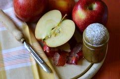 Δονητής ζάχαρης, μήλα και μαχαίρι φλούδας στον ξύλινο τεμαχίζοντας πίνακα Στοκ Εικόνες