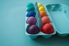 Δονούμενα βαμμένα χέρι ζωηρόχρωμα αυγά Πάσχας σε ένα κιβώτιο αυγών χαρτονιού που αντιμετωπίζεται στοκ εικόνες