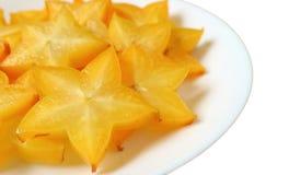 Δονούμενα πορτοκαλιά κίτρινα φρέσκα ώριμα φρούτα αστεριών που τεμαχίζονται στα κομμάτια που εξυπηρετούνται στο άσπρο πιάτο στοκ φωτογραφία