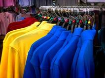 Δονούμενα πουκάμισα πόλο που κρεμούν στο κυρτό ράφι χάλυβα Στοκ φωτογραφία με δικαίωμα ελεύθερης χρήσης