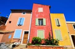 Δονούμενα σπίτια Rousillon, Προβηγκία, Γαλλία με τα κόκκινα και κίτρινα χρώματα Στοκ Εικόνες