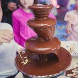 Δονούμενη εικόνα της πηγής Fontain σοκολάτας στη γιορτή γενεθλίων παιδιών παιδιών με ένα παιχνίδι παιδιών γύρω και marshmallows κ Στοκ εικόνα με δικαίωμα ελεύθερης χρήσης