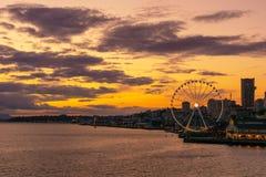 Δονούμενος και ζωηρόχρωμος ορίζοντας του Σιάτλ waterfont με τη μεγάλη ή ρόδα Ferris στο ηλιοβασίλεμα ή το σούρουπο από τον κόλπο  στοκ φωτογραφία με δικαίωμα ελεύθερης χρήσης