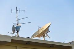 Δορυφορικές κεραίες πιάτων και TV στη στέγη σπιτιών με το υπόβαθρο μπλε ουρανού Στοκ Εικόνες