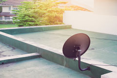 Δορυφορική κεραία πιάτων πάνω από το κτήριο και τον ήλιο Στοκ εικόνα με δικαίωμα ελεύθερης χρήσης
