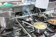 Δοχεία και τηγάνια στη σόμπα στην κουζίνα εστιατορίων, ο αρχιμάγειρας που λειτουργεί το ι Στοκ Φωτογραφία