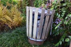 Δοχείο απορριμμάτων πάρκων σε μια ρύθμιση κήπων Στοκ εικόνα με δικαίωμα ελεύθερης χρήσης