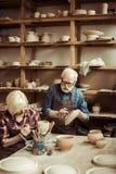 Δοχείο αργίλου ζωγραφικής γυναικών με τον ανώτερο αγγειοπλάστη Στοκ Φωτογραφία