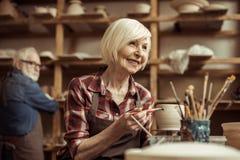 Δοχείο αργίλου ζωγραφικής γυναικών με τον ανώτερο αγγειοπλάστη Στοκ φωτογραφία με δικαίωμα ελεύθερης χρήσης