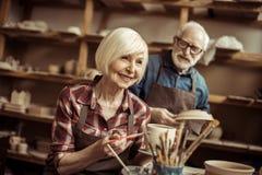 Δοχείο αργίλου ζωγραφικής γυναικών με τον ανώτερο αγγειοπλάστη Στοκ εικόνα με δικαίωμα ελεύθερης χρήσης