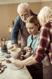 Δοχείο και παππούδες και γιαγιάδες αργίλου ζωγραφικής κοριτσιών που βοηθούν στο εργαστήριο Στοκ εικόνα με δικαίωμα ελεύθερης χρήσης
