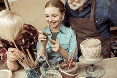 Δοχείο και παππούδες και γιαγιάδες αργίλου ζωγραφικής κοριτσιών που βοηθούν στο εργαστήριο Στοκ φωτογραφία με δικαίωμα ελεύθερης χρήσης