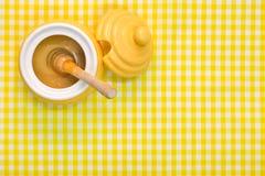 Δοχείο και dipper μελιού στο κίτρινο υπόβαθρο με το διάστημα αντιγράφων Στοκ Εικόνα