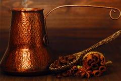 Δοχείο καφέ Τούρκου και φασόλια καφέ με τα καρυκεύματα στον πίνακα στοκ εικόνες με δικαίωμα ελεύθερης χρήσης