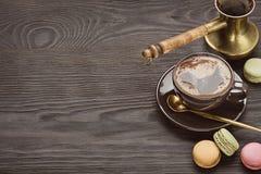 Δοχείο καφέ, φλυτζάνι του καυτού καφέ και κουτάλι στο πιατάκι, macaroons στο σκοτεινό ξύλινο πίνακα διάστημα αντιγράφων Στοκ εικόνες με δικαίωμα ελεύθερης χρήσης