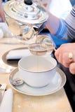 Δοχείο του φρέσκου τσαγιού με το διηθητήρα τσαγιού που χύνεται στο φλυτζάνι και το πιατάκι Τσάι προγευμάτων απογεύματος Στοκ εικόνες με δικαίωμα ελεύθερης χρήσης