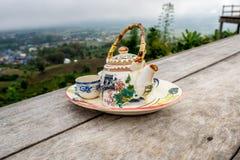 Δοχείο τσαγιού με το φλυτζάνι που τίθεται στον ξύλινο πίνακα μπροστά από τη θέα βουνού στοκ φωτογραφία