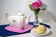 Δοχείο τσαγιού στο πιάτο με τα λουλούδια και scones στοκ φωτογραφία με δικαίωμα ελεύθερης χρήσης