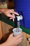 Δοχείο ψύξης νερού που εκκενώνει σε ένα φλυτζάνι Στοκ εικόνα με δικαίωμα ελεύθερης χρήσης