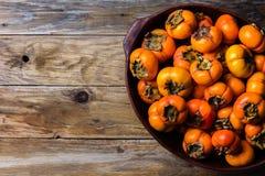 Δοχείο persimmon νωπών καρπών kaki στο ξύλινο υπόβαθρο διάστημα αντιγράφων Στοκ εικόνες με δικαίωμα ελεύθερης χρήσης