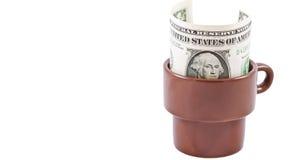 Δολάριο σε ένα φλυτζάνι καφέ που αφήνεται ως άκρη Στοκ Εικόνες