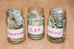 Δολάριο στο βάζο γυαλιού με το σπίτι, αυτοκίνητο, εκπαίδευση, γάμος, ετικέτα ταξιδιού, Στοκ Εικόνες