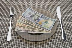 Δολάριο Bill σε ένα πιάτο με το δίκρανο και το μαχαίρι Στοκ Εικόνα