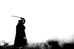 Δολοφόνος γυναικών που κρατά το ιαπωνικό ξίφος σε ένα μετα-apocalyptical τοπίο Στοκ εικόνα με δικαίωμα ελεύθερης χρήσης
