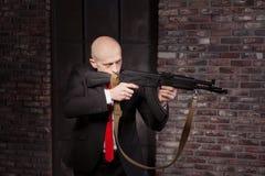 Δολοφόνος στο κοστούμι και τον κόκκινο βλαστό δεσμών ένα πολυβόλο Στοκ Φωτογραφίες