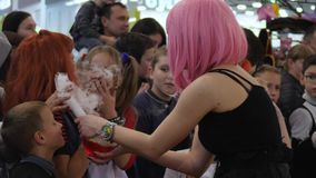 Δράση με τον καπνό για των παιδιών στη λεωφόρο στον εορτασμό αποκριές, κορίτσι στη ρόδινη περούκα με τη βράζοντας φιάλη γυαλιού φιλμ μικρού μήκους