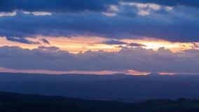 Δραματικά χειμαρρώδη σύννεφα ηλιοβασιλέματος πέρα από το λοφώδες τοπίο απόθεμα βίντεο