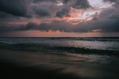 Δραματικά χρυσά σύννεφα ηλιοβασιλέματος που απεικονίζονται στη θάλασσα νερού tropic στοκ φωτογραφία