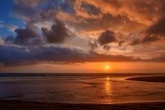 Δραματικά χρυσά σύννεφα ηλιοβασιλέματος που απεικονίζονται στη θάλασσα νερού tropic στοκ εικόνες