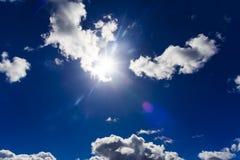 Δραματική φλόγα ήλιων με τα χνουδωτά σύννεφα στο βαθύ μπλε ουρανό, υψηλό γ Στοκ Φωτογραφίες