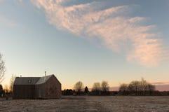 Δραματική χειμερινή σκηνή με το χιονώδες ξύλινο σπίτι και το ρόδινο ουρανό Στοκ φωτογραφία με δικαίωμα ελεύθερης χρήσης